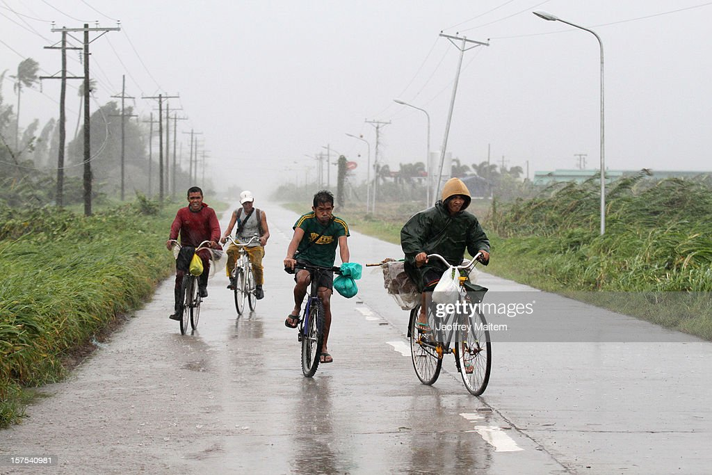 Residents are seen along the highway after heavy rains and strong winds, brought about by Typhoon Bopha, hit the township of Mabini on December 04, 2012 in the province of Compostela Valley in the southern Philippines. Typhoon Bopha made landfall in the southern Philippines earlier today, bringing heavy rain and wind gusts of 210 km/h (130mph). So far at least 40 have died and over 40,000 people have been forced into shelters.