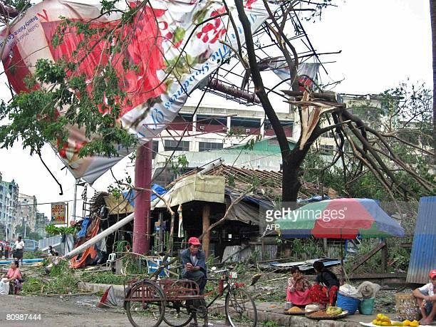 Residents are seen near uprooted trees and downed power lines in a street in Yangon on May 4 2008 Myanmar residents awoke to devastation after...