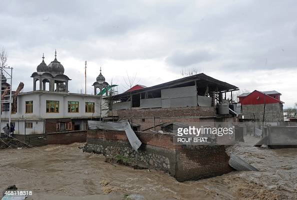 Residents attempt to reach their inundated homes as waters rise in a neighbourhood of Srinagar on March 30 2015 At least 10 people have been buried...