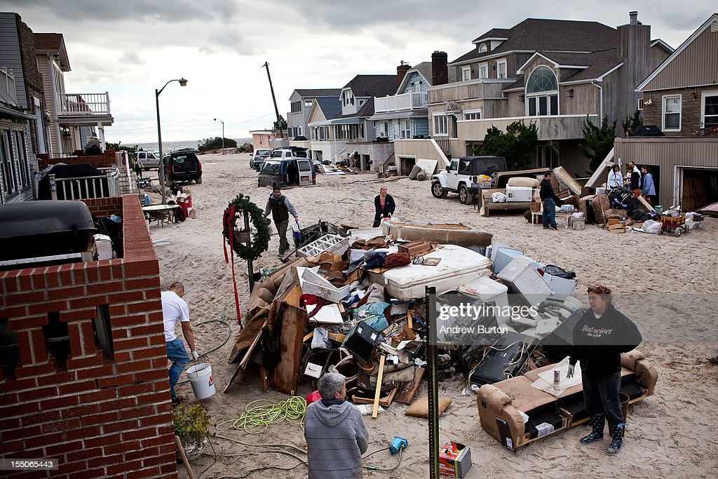 Residents attempt to restore order to their street which experienced heavy flooding and dune erosion due to Hurricane Sandy on October 31 2012 in...