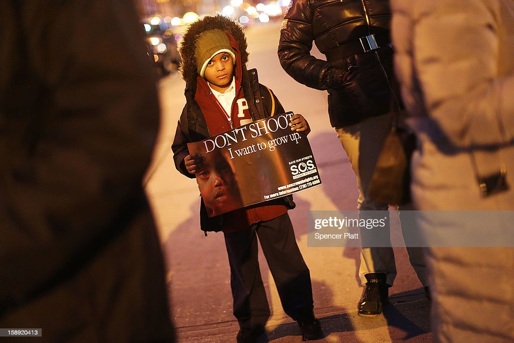 Residents attend a rally and vigil on the sidewalk near where two teens were shot on New Year's Day on January 03, 2013 in the Crown Heights neighborhood of the Brooklyn borough of New York City. The gathering was sponsored by the local community group Save Our Streets Crown Heights (S.O.S.) which is a community-based effort to end gun violence. S.O.S. holds the gatherings at all shooting locations in Crown Heights to draw attention to the violence and to encourage a community response to the shootings. While murders were down for 2012 in New York City, robberies, burglaries and felony assaults rose.