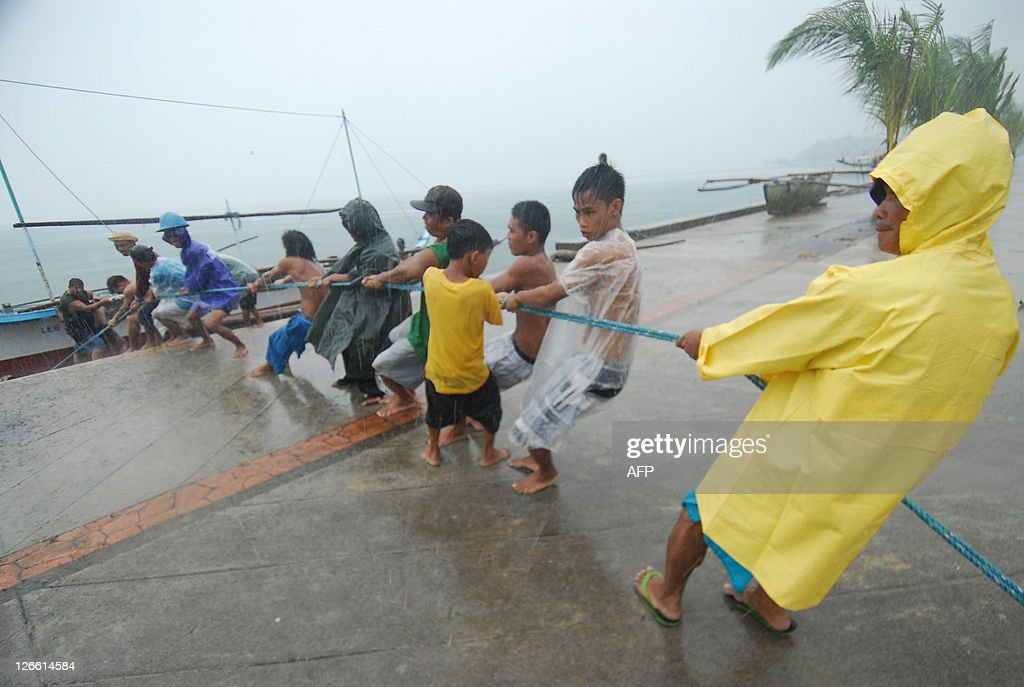Residents brave heavy rains and strong winds as they pull a motor boat from the pier side in preparation for to Typhoon Nesat in Legazpi City Albay...