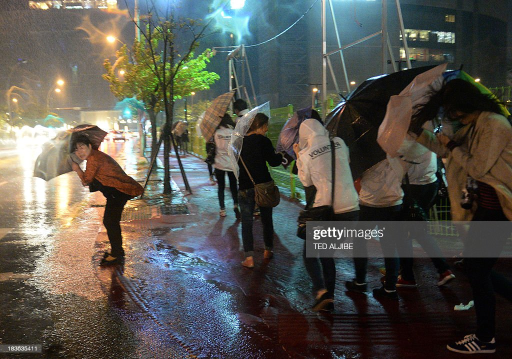 Residents brave strong winds and heavy rain brought about by Typhoon Danas in Busan on October 8, 2013, before the typhoon is expected to pass through the coastal city. Packing winds of up to 180 kilometres (112 miles) per hour near its centre, Danas was churning northwest towards the southern Okinawa island chain and was expected to reach a point off the western coast of Kyushu island by early on October 9. AFP PHOTO/TED ALJIBE
