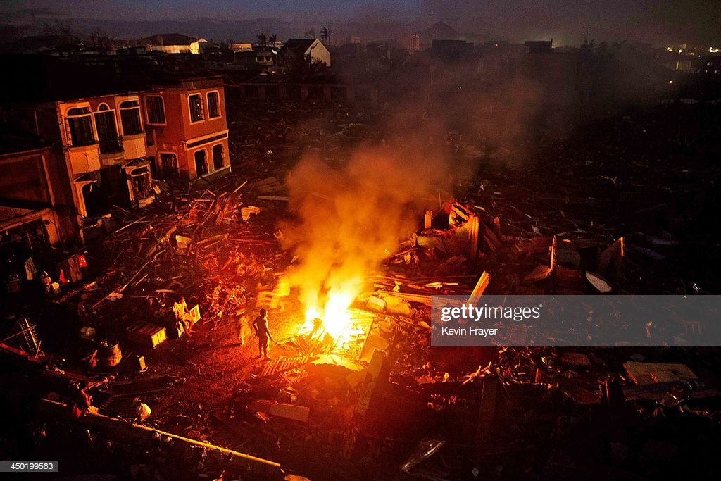 Residents burn scrap wood on a fire in a devastated area in the aftermath of Typhoon Haiyan on November 17 2013 in Tacloban Philippines Typhoon...