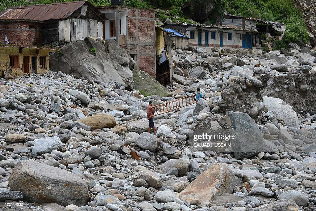 Residents carry a ladder as they set off to rescue a stranded mule in Sonprayag on July 2, 2013, in a flood affected area of the northern Indian state of Uttrakhand. Construction along river banks will be banned in a devastated north Indian state amid concerns unchecked development fuelled last month's flash floods and landslides that killed thousands, the state's top official said. The Chief Minister of Uttarakhand, Vijay Bahuguna, also announced that a regulatory body would be set up to scrutinise future construction as the Himalayan state begins the herculean task of rebuilding following the June 15 floods. AFP PHOTO/SAJJAD HUSSAIN