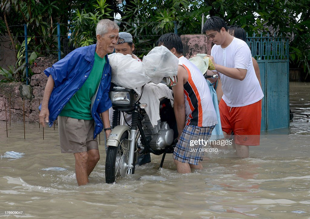 Residents carry a motorcycle over floodwaters in the farming town of Novaleta, some 26 kilometres outside Manila on August 19, 2013. Torrential rain paralysed large parts of the Philippine capital on August 19 as neck-deep water swept through homes, while floods in northern farming areas claimed at least one life. AFP PHOTO / Jay DIRECTO