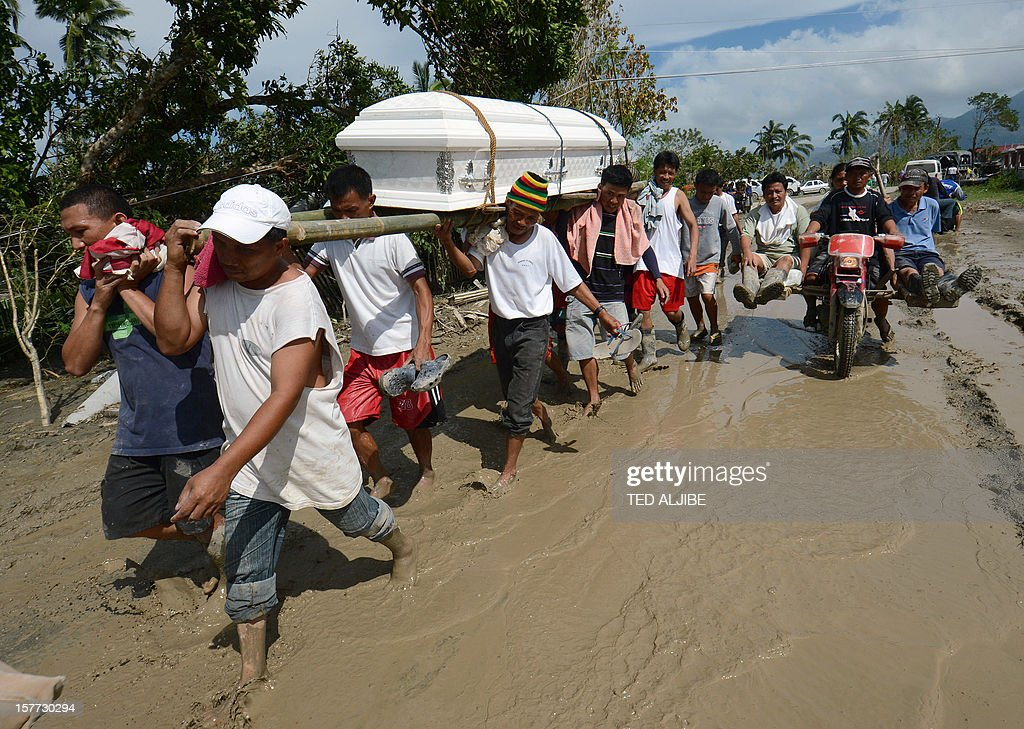 Residents carry a relative's coffin along a muddy road in the town of New Bataan, compostela province on December 6, 2012. Nearly 200,000 people are homeless and more than 300 dead after the Philippines suffered its worst typhoon this year, authorities said on December 6, reaching out for international aid to cope with the scale of the disaster.