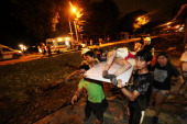 Residents carry a wounded person following a blast in the city of Kaohsiung in southern Taiwan early on August 1 2014 The explosion that is believed...