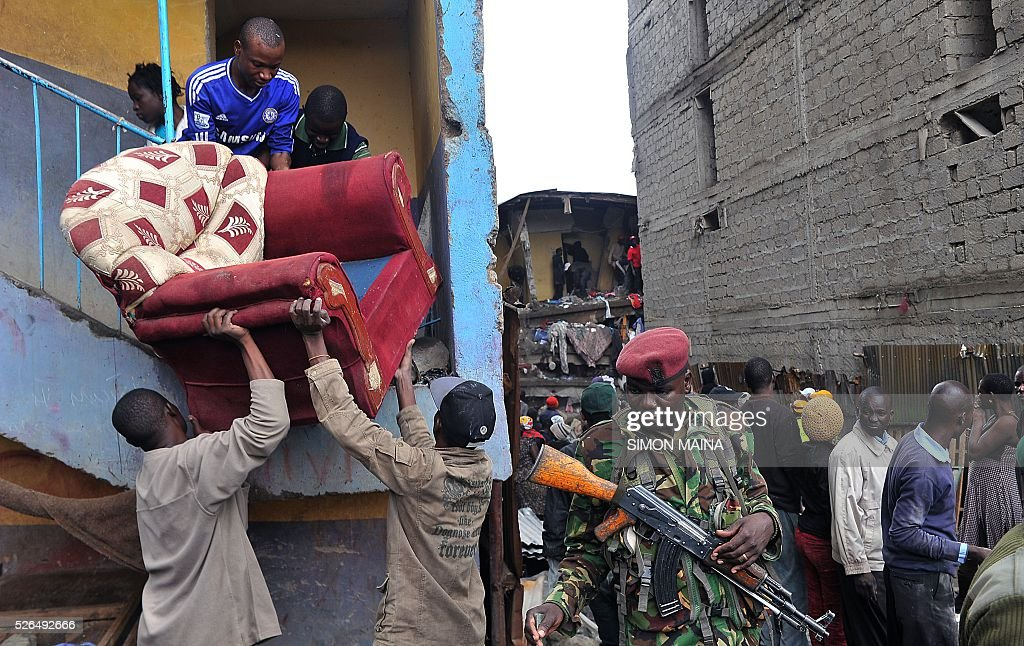 Residents carry an armchair as they are evacuated after a building collapsed in Nairobi on April 30, 2016. Rescuers in the Kenyan capital made desperate efforts to free survivors including a woman and child trapped in a building that collapsed in storms that have left a total of 17 people dead. / AFP / SIMON