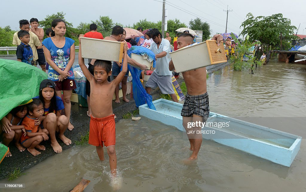 Residents carry belongings after floodwaters inundated their homes in the farming town of Novaleta, some 26 kilometres outside Manila on August 19, 2013. Torrential rain paralysed large parts of the Philippine capital on August 19 as neck-deep water swept through homes, while floods in northern farming areas claimed at least one life. AFP PHOTO / Jay DIRECTO