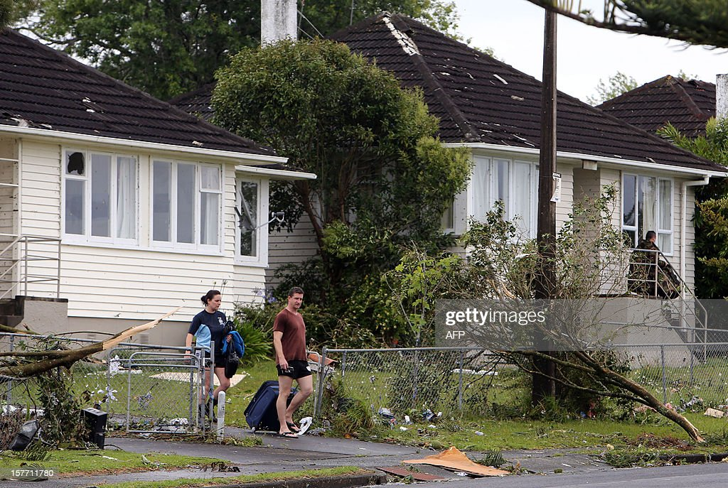 Residents carry belongings as they leave their damaged houses in Hobsonville, Auckland on December 6, 2012 after packed wind gusts of up to 110 kilometres (70 miles) per hour, struck suburban Hobsonville in the afternoon. A freak storm described by police as a tornado hit New Zealand's largest city Auckland on December 6 causing 'utter devastation', with three people reportedly killed in ferocious winds. AFP PHOTO / Michael Bradley