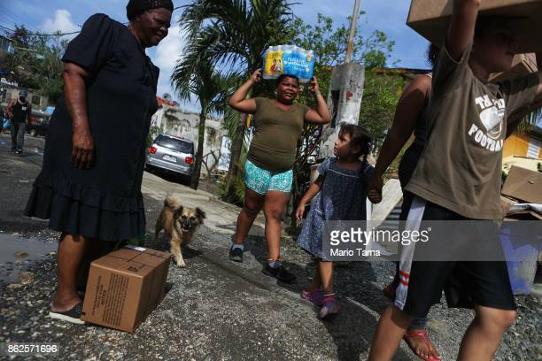 Residents carry food and water provided by FEMA to residents in a neighborhood without grid electricity or running water on October 17 2017 in San...