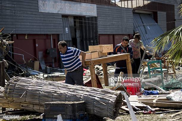 Residents carry furniture between debris caused by the sea in the port of Coquimbo some 445 km north of Santiago during the eve's earthquake on...
