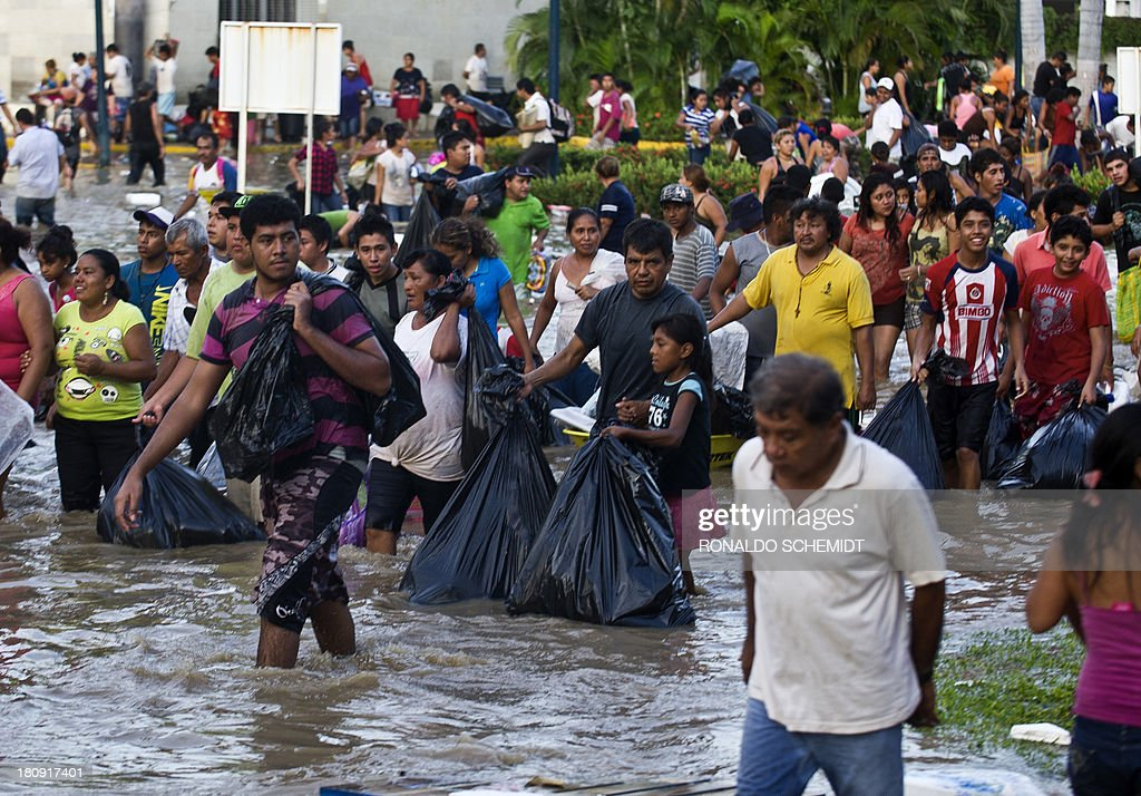 Residents carry goods after looting a supermarket in Acapulco, state of Guerrero, Mexico, on September 17, 2013 as heavy rains hit the country. Mexican authorities scrambled Tuesday to launch an air lift to evacuate tens of thousands of tourists stranded amid floods in the resort of Acapulco following a pair of deadly storms. The official death toll rose to 47 after the tropical storms, Ingrid and Manuel, swarmed large swaths of the country during a three-day holiday weekend, sparking landslides and causing rivers to overflow in several states.