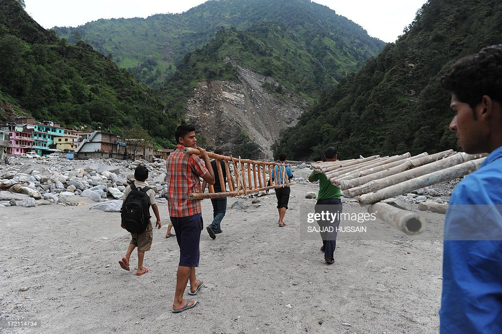 Residents carry ladders as they prepare to rescue a mule from the Mandakni river in Sonprayag on July 2, 2013, in a flood affected area of the northern Indian state of Uttrakhand. Construction along river banks will be banned in a devastated north Indian state amid concerns unchecked development fuelled last month's flash floods and landslides that killed thousands, the state's top official said. The Chief Minister of Uttarakhand, Vijay Bahuguna, also announced that a regulatory body would be set up to scrutinise future construction as the Himalayan state begins the herculean task of rebuilding following the June 15 floods.