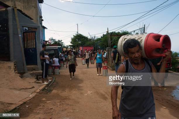 Residents carry Petroleos de Venezuela SA gas canisters after a weekly delivery in La Guaira Venezuela on Friday Oct 6 2017 As Venezuela prepares to...