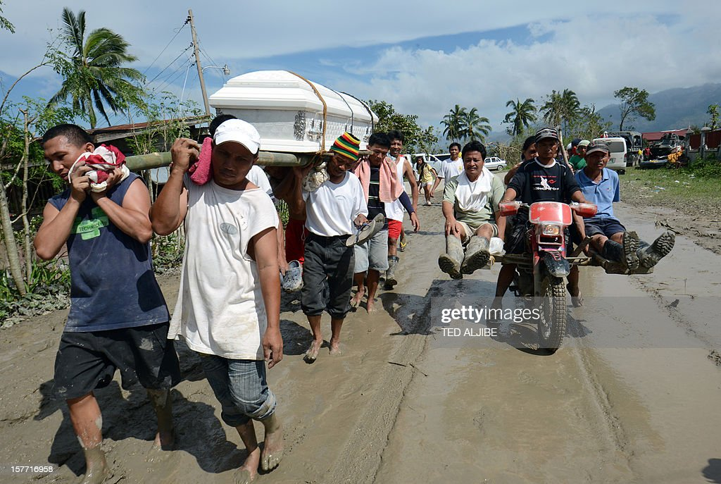 Residents carry the coffin of a dead relative in New Bataan town, compostela province on December 6, 2012. Nearly 200,000 people are homeless and more than 300 dead after the Philippines suffered its worst typhoon this year, authorities said on December 6, reaching out for international aid to cope with the scale of the disaster.