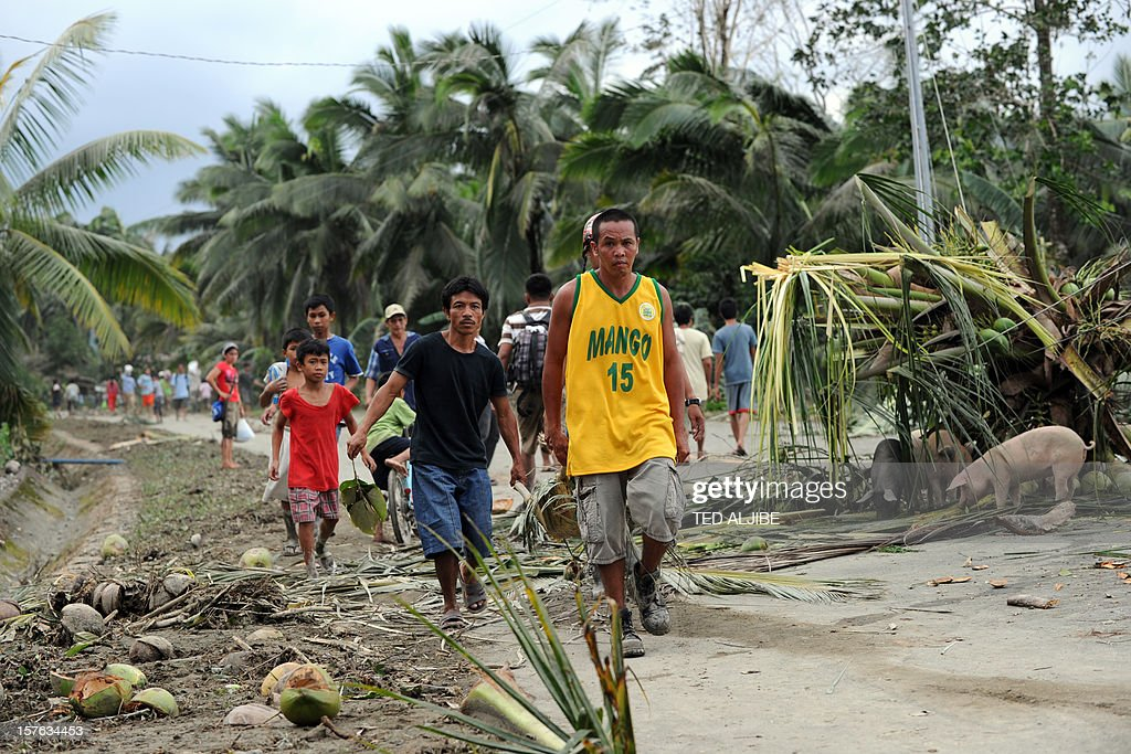 Residents carry the dead body of child, victim of flash floods on a makeshift stretcher in the village of Andap, New Bataan town, Compostela Valley province on December 5, 2012, a day after the powerful Typhoon Bopha hit the province. At least 274 people have been killed and hundreds remain missing in the Philippines from the deadliest typhoon to hit the country this year, the civil defence chief said December 5.