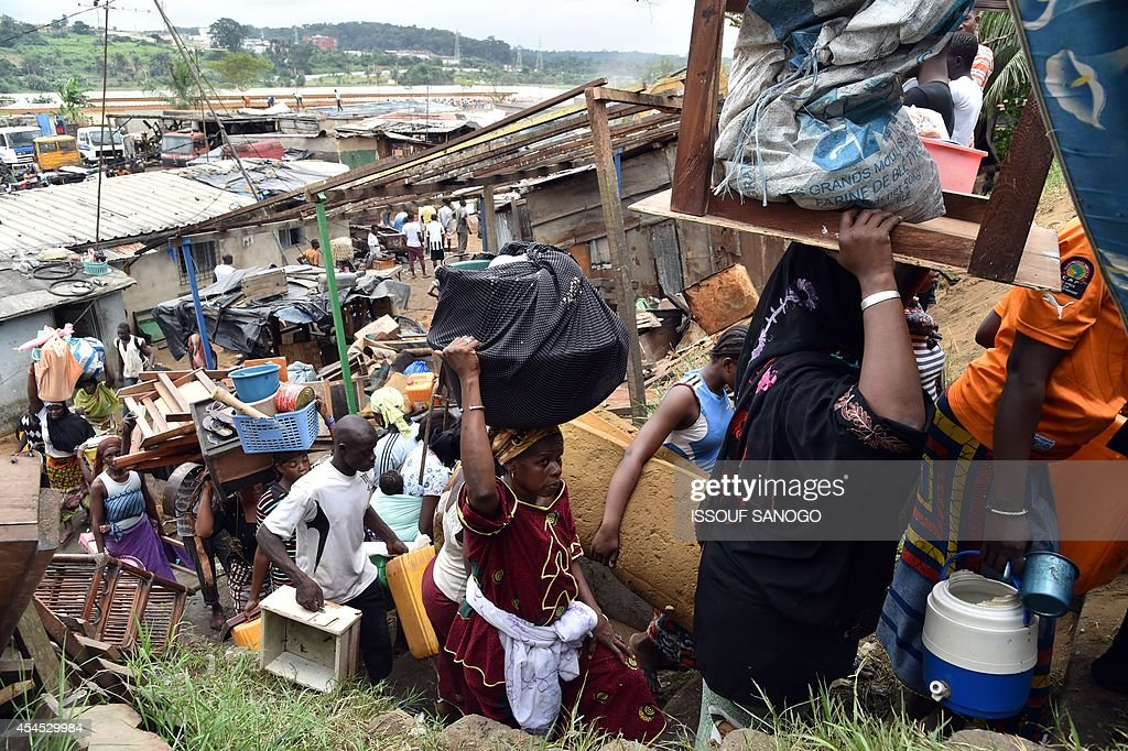 Residents carry their belongings after leaving their homes as a destruction operation is taking place on September 2, 2014 in Attecoube, a poor sector of Abidjan, in order to remove unstable habitations built on hill slopes deemed as landslide prone. About 39 people died on June 2014 in Abidjan because of landslides since the beginning of the rainy season. 350,000 people live in Attecoube, most of them in terrible conditions and on unstable ground, making them particularly vulnerable to floods and landslides.