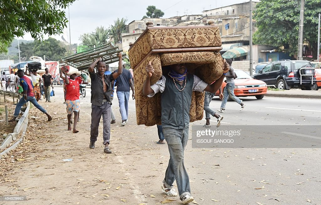 Residents carry their belongings after leaving their homes as a destruction operation is taking place on September 2, 2014 in Attecoube, a poor sector of Abidjan, in order to remove unstable habitations built on hill slopes deemed as landslide prone. A bout 39 people have died on June in Abidjan because of landslides since the beginning of the rainy season. 350,000 people live in Attecoube, most of them in terrible conditions and on unstable ground, making them particularly vulnerable to floods and landslides.