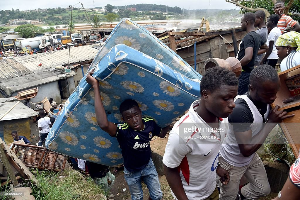 Residents carry their belongings after leaving their homes as a destruction operation is taking place on September 2, 2014 in Attecoube, a poor sector of Abidjan, in order to remove unstable habitations built on hill slopes deemed as landslide prone. About 39 people died on June 2014 in Abidjan because of landslides since the beginning of the rainy season. 350,000 people live in Attecoube, most of them in terrible conditions and on unstable ground, making them particularly vulnerable to floods and landslides. AFP PHOTO / ISSOUF SANOGO
