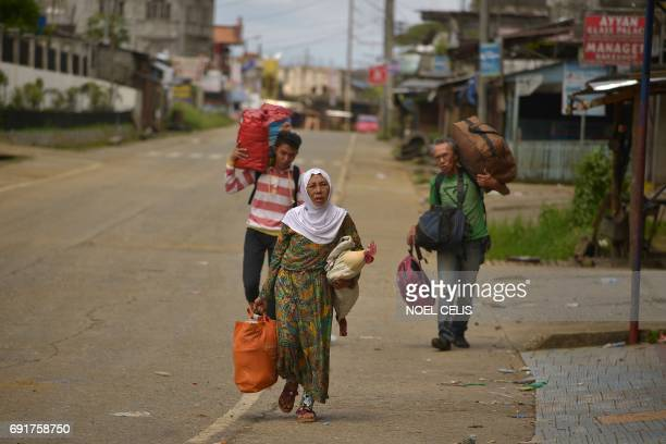 Residents carry their belongings as they walk along a deserted street as they flee from their homes in Marawi on the southern island of Mindanao on...