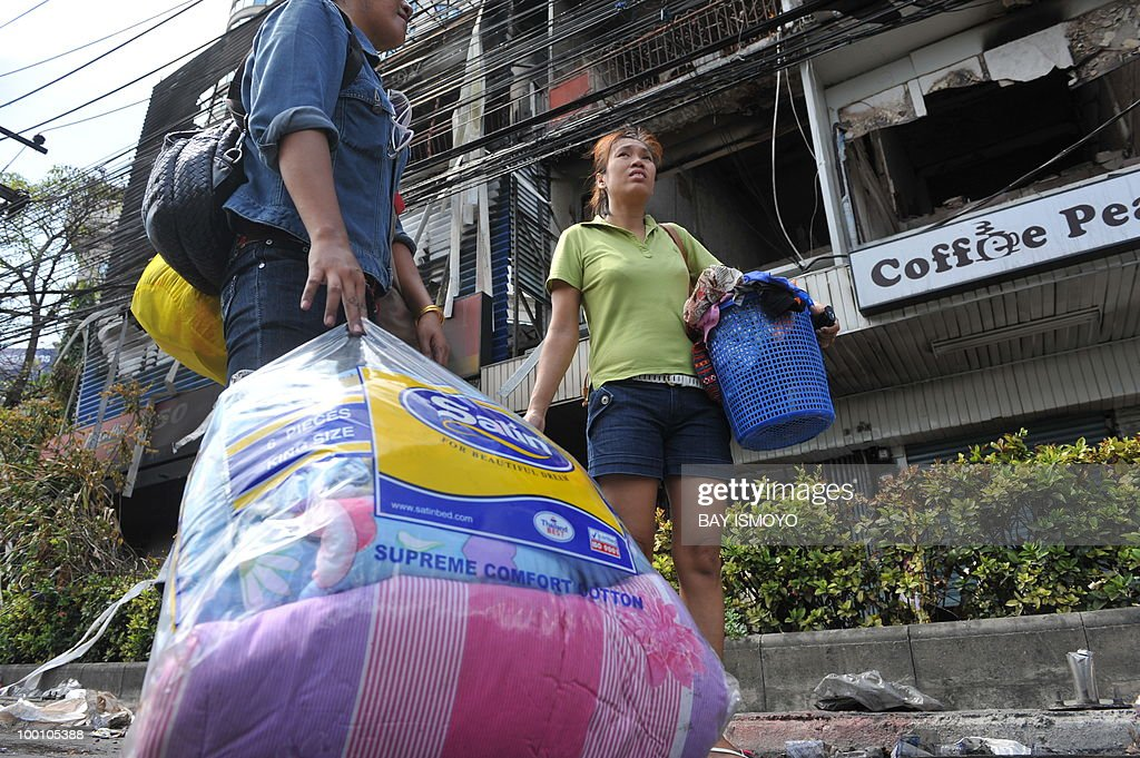 Residents carry their belongings from their damaged and burnt shop house downtown Bangkok on May 21, 2010. Thailand picked up the pieces after violence and mayhem triggered by a crackdown on anti-government protests, as the focus swung to recovery and reconciliation in a divided nation. AFP PHOTO / Bay ISMOYO