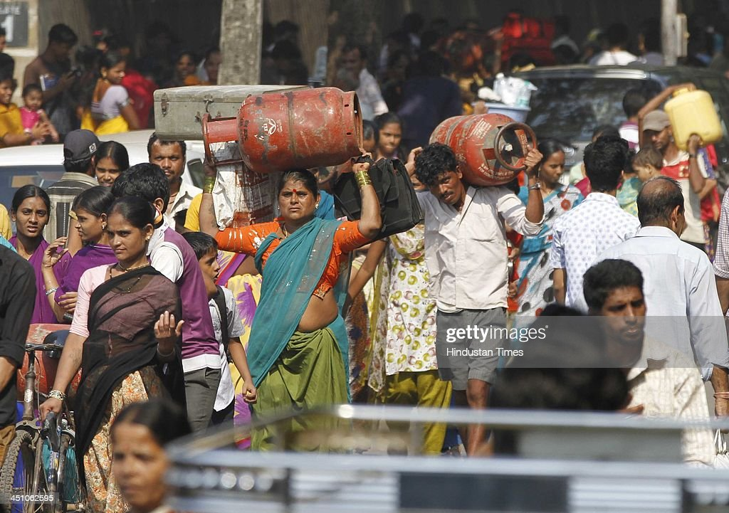 Residents carry their cylinders and luggage as fire broke out at Ambedkar Nagar slum, Cuffe Parade on November 21, 2013 in Mumbai, India. Several huts were gutted in a fire that broke out in the settlement. About 10 fire engines and eight water tankers have been rushed to the spot to douse the flames.
