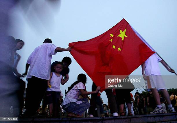 Residents celebrate the Guangan leg of Beijing Olympic torch relay at a square on August 2 2008 in Guangan of Sichuan Province China The threeday...