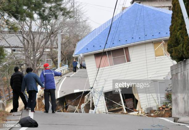 residents check the damaged done on a road a house in Sukagawa city Fukushima prefecture in northern Japan on March 11 2011 A massive 89magnitude...
