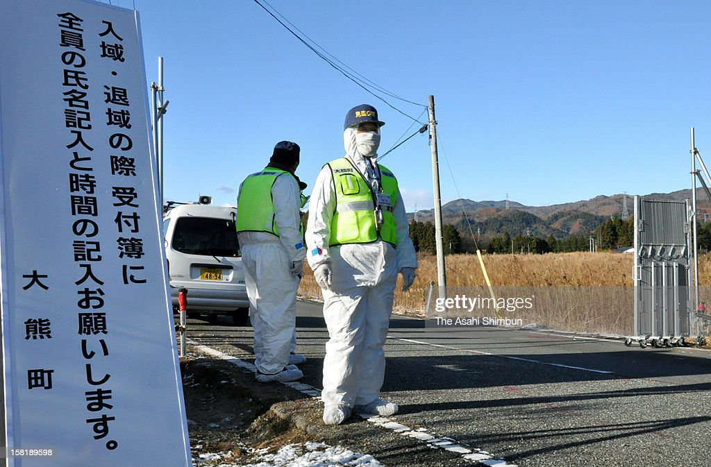 Residents check the traffic at a gate in Okuma City, where the crippled Fukushima Daiichi Nuclear Power Plant is located, on December 10, 2012 in Okuma, Fukushima, Japan. Japanese government reclassified the area where 96 percent of Okuma city residents used to live as 'residents will face difficulties in returning for a long time' according to the radiation contamination level.