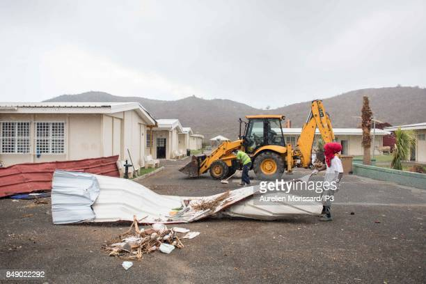 Residents clean the rubbles at Saint Martin III's College in the Orleans neighborhood eleven days after the passage of hurricane Irma on September 16...