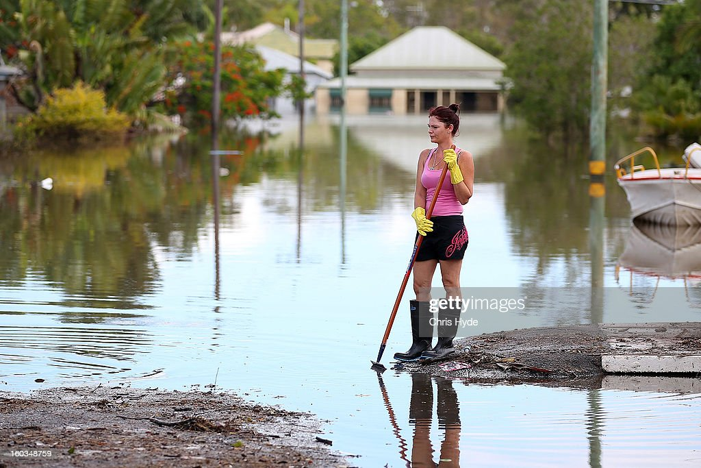 Residents clean up debris in their street as parts of southern Queensland experiences record flooding in the wake of Tropical Cyclone Oswald on January 30, 2013 in Bundaberg, Australia. Flood waters peaked at 9.53 metres in Bundaberg yesterday and began receding overnight, as residents and relief teams prepare to clean-up debris. Four deaths have been confirmed in the Queensland floods and the search is on for two men though to be missing in floodaters in Gatton.