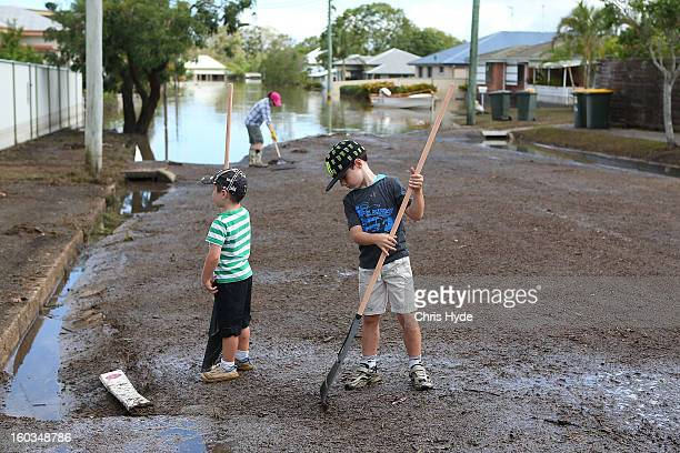 Residents clean up debris in their street as parts of southern Queensland experiences record flooding in the wake of Tropical Cyclone Oswald on...