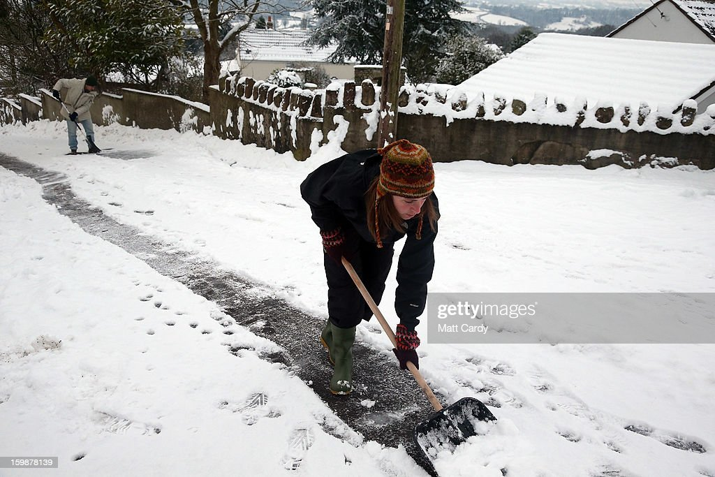 Residents clear snow on a road near Holcombe on January 22, 2013 in Somerset, England. Snow and ice is continuing to cause disruption to some parts of the UK with more snow forecast for the South West tonight.