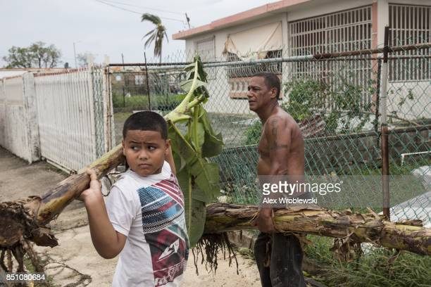 Residents clear the streets after Hurricane Maria made landfall September 21 2017 in the Guaynabo suburb of San Juan Puerto Rico The majority of the...