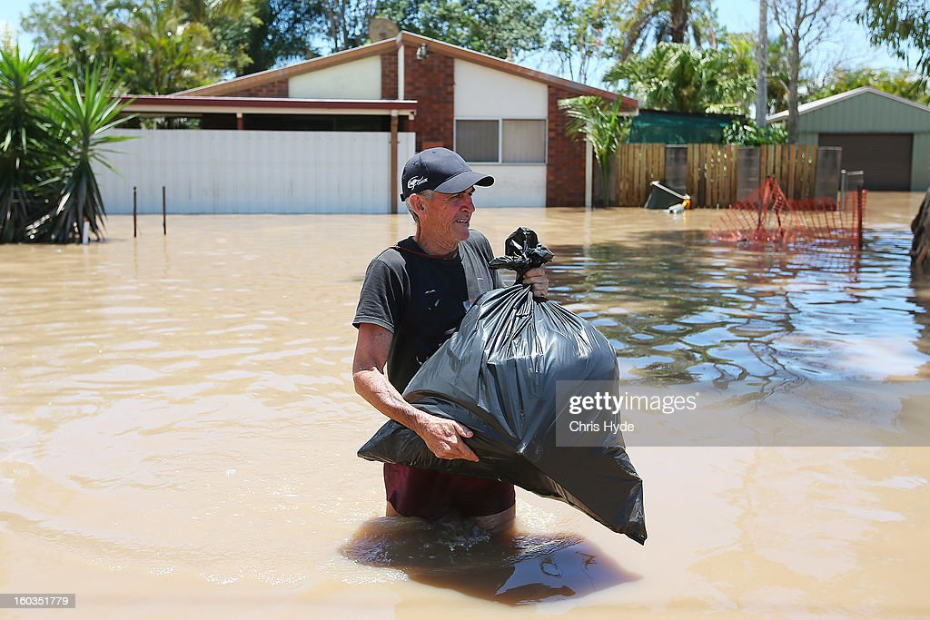 Residents collect belongings from their homes their as parts of southern Queensland experiences record flooding in the wake of Tropical Cyclone Oswald on January 30, 2013 in Bundaberg, Australia. Flood waters peaked at 9.53 metres in Bundaberg yesterday and began receding overnight, as residents and relief teams prepare to clean-up debris. Four deaths have been confirmed in the Queensland floods and the search is on for two men though to be missing in floodaters in Gatton.