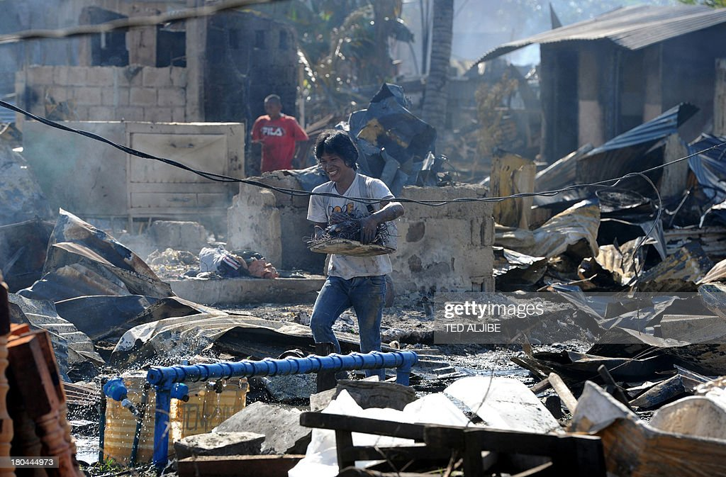 Residents collect salvageable materials from their destroyed house gutted by fire at the height of firefight between government forces and Muslim rebels are seen in Zamboanga City in southern island of Mindanao on September 13, 2013, as the stand-off enter its fifth day. Philippine President Benigno Aquino September 13, visited the southern city of Zamboanga where government troops are battling followers of a Muslim rebel leader opposed to peace talks.