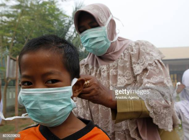 Residents cover their face with masks due to smoke from peat forest fire in Aceh Indonesia on July 25 2017 The number of hotspots in Indonesia...
