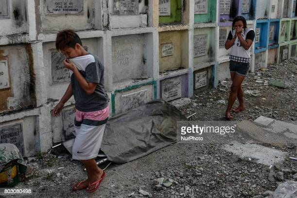 Residents cover their noses as they walk past the body of a shooting victim unclaimed for months to be buried in a mass grave in Navotas north of...