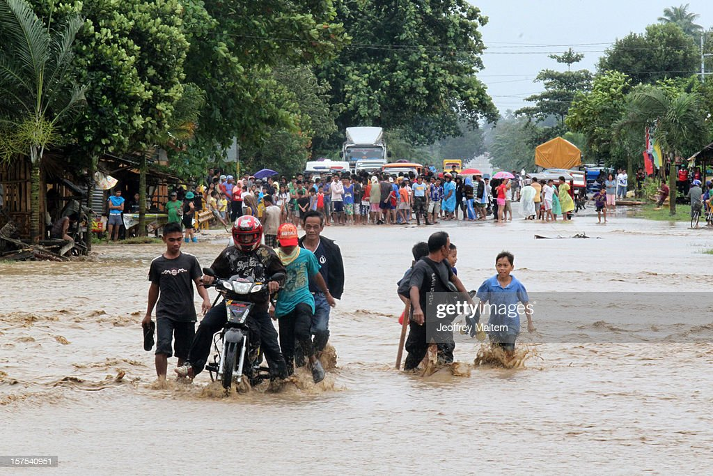 Residents cross a flooded road after heavy rains and strong winds, brought about by Typhoon Bopha, hit the township of Mabini on December 04, 2012 in the province of Compostela Valley in the southern Philippines. Typhoon Bopha made landfall in the southern Philippines earlier today, bringing heavy rain and wind gusts of 210 km/h (130mph). So far at least 40 have died and over 40,000 people have been forced into shelters.