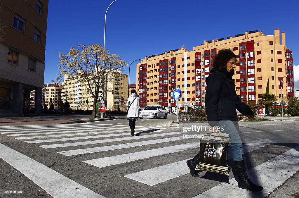Residents cross a pedestrian crossing near apartment blocks in Madrid, Spain, on Monday, Jan. 13, 2014. Spain's rental market is growing as government-spending cuts, a 26 percent jobless rate and subdued mortgage lending make home buying more difficult. Photographer: Angel Navarrete/Bloomberg via Getty Images
