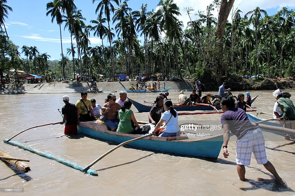 Residents cross a river on board a small boat after typhoon Bopha destroyed a bridge, on December 8, 2012 in the town of Baganga, Davao Oriental province, Philippines. More than 500 people have been killed and scores of others remain missing after Typhoon Bopha, the strongest storm to hit the Philippines this year, pounded the region. The United Nations Office for the Coordination of Humanitarian Affairs reported that about 5.3 million people affected and 533 missing.