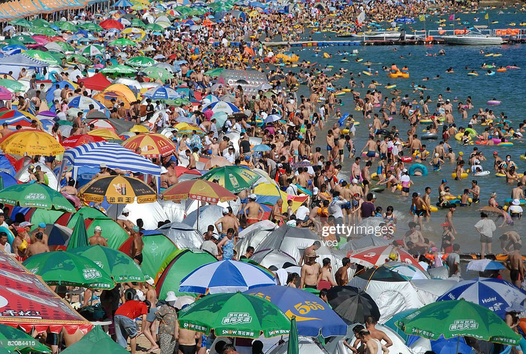 Residents crowd on to the Fujiazhuang beach to cool themselves on July 26, 2008 in Dalian, Liaoning province, northeast China. Over 100,000 people visited Dalian's beaches today, the highest number recorded so far this summer.