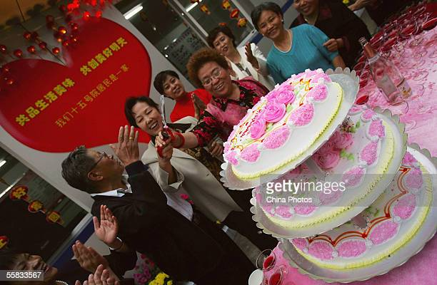 Residents cut butter cakes to celebrate the National Day during a community activity on September 30 2005 in Beijing China Various celebrations are...