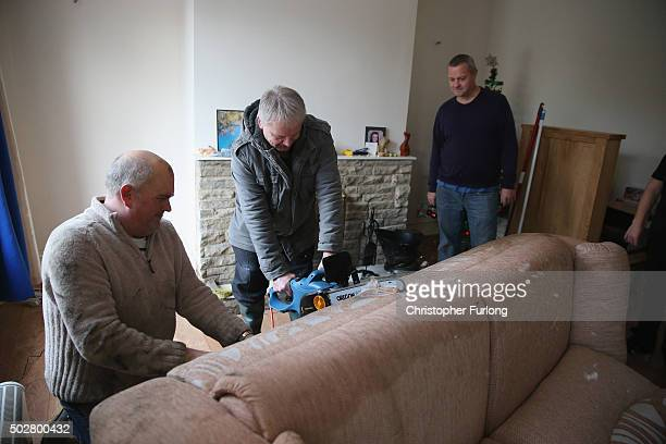 Residents cut up damaged furniture with a chainsaw caused by flood waters in the village of Elland Flood waters from the River Calder overflowed into...