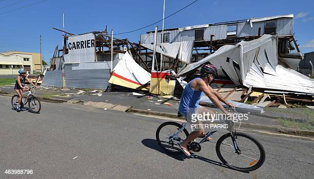 Residents cycle past a cyclone damaged business in the northern Queensland town of Rockhampton on February 21 2015 Australia was assessing the damage...