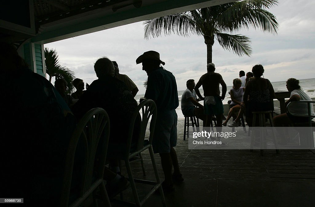 Residents drink at a seaside bar in advance of the arrival of Hurricane Wilma which is churning in the Gulf of Mexico as a Category 2 storm October...