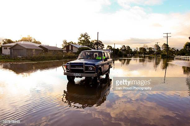 Residents drive a fourwheeldrive through flooded streets on January 11 2011 in Oakey Australia 10 people so far have been confirmed dead in towns in...