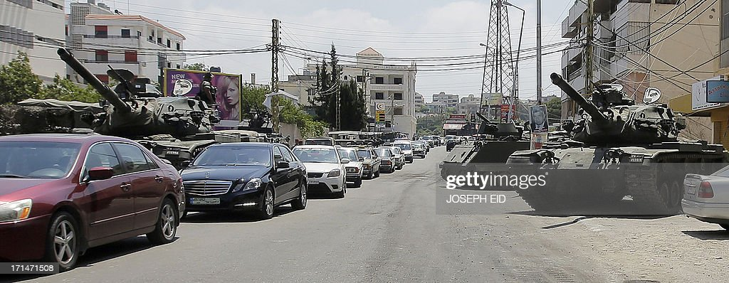 Residents drive past Lebanese army tanks securing the area near the Bilal bin Rabah mosque in the Abra district of the southern city of Sidon on June 25, 2013, after troops seized control of the headquarters of a radical Sunni sheikh whose supporters battled the army for two days, killing 16 soldiers.